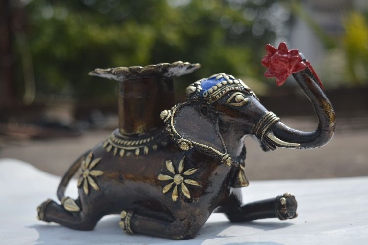 this is Elephant with candle stand and tealight holder. is perfect for any corner of your living room. is  exclusive piece of Dhokra art work. This piece is made as one piece only, This is Total handmade,Ecofriendly,Tribal,Antique and Very Ethnic Exclusive range of Product Design by BHANSALI HANDICRAFT.   >WEIGHT	                - 1.150kg  >DIMENSIONS (CM)	- W: 4 x H: 4 x L: 8 >ART WORK	                - Dhokra  >TYPE	                        - Home Decor  >MATERIAL	                - Bell metal  >THEME	                - Animal Figure >COLOUR                      - Multi colour