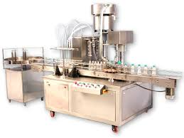 The Electronic PLC Based Filling Machine is compact and highly efficient machine with elegant look. This multi functional multi featured machine meets the GMP requirements of filling for glass, plastic or Aluminum bottles.  The flow of liquid is measured and converted in to electronic signals being controlled by micro computer base circuitry. Minimum adjustment required to set different capacities from 500ml to 5 Ltr with varying containers. The entire range can be set on the same machine without any change parts with help of flow meter pulses.   Operation:-  Nozzle goes upwards slowly from the bottom level of bottle towards neck during filling to minimize foaming adjustable nozzle is reciprocating according to filling dose  The filling synchronized with conveyor drive and conveyor drive controlled by Ac frequency drive. The speed can be set in terms of bottles per minute. The conveyor drive consists of a hallow shaft, geared motor controlled by Ac frequency drive. A knob can set the speed of conveyor.