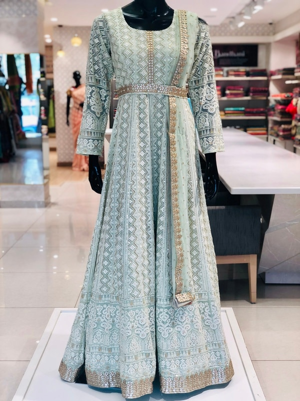 A Stunning Mint Green Gown with bold Gota Patti work along the border and the belt, crafted on pure Georgette. Perfect for Sangeet or Mehendi functions.
