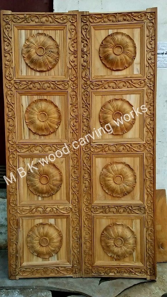 Wooden teak wood carving main door double shutter best quality teak wood used and nice looking carving design meddle and side carving door size 80 inches height 40 inches width 40 thickness without hardware no polishing only Door